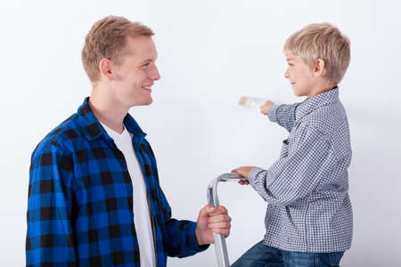 Father learning his son how to paint a wall, horizontal photo