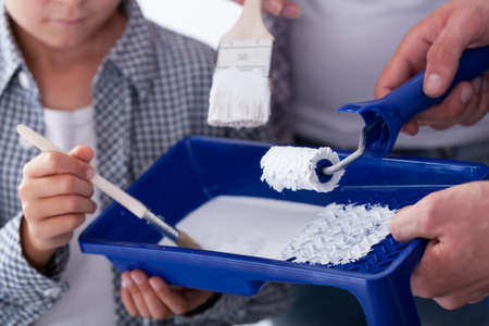 priming paint: Priming paint in paint tray and paintbrushes Stock Photo