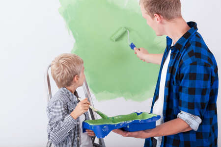 man painting: Dad and son painting wall in childs room