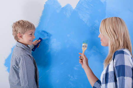 Mother and son having fun from painting the wall, horizontal photo