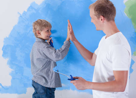 family of five: Young father giving high five to his little son during working together Stock Photo