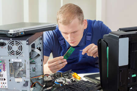 repair computer: Young blonde IT specialist installing ram memory