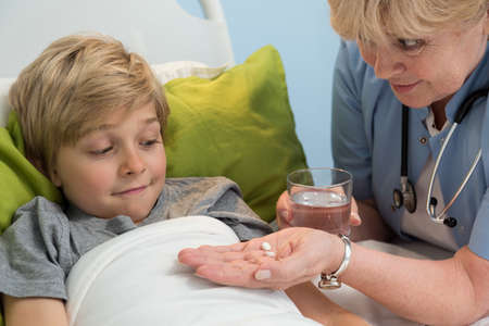 doctor giving pills: Sweet blonde patient and his caring doctor
