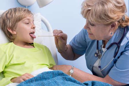 Examination of the throat of ill boy photo