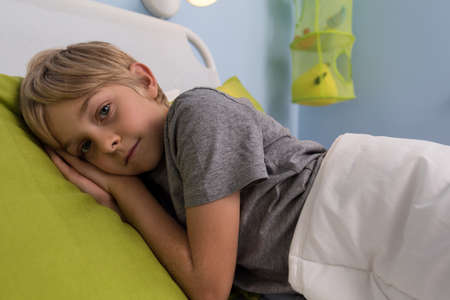 Portrait of ill child lying in hospital bed Stock Photo