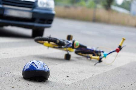 Ein kleines Fahrrad und einen Helm auf der Straße liegen Standard-Bild - 33303304