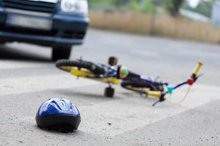 A small bike and a helmet lying on the road