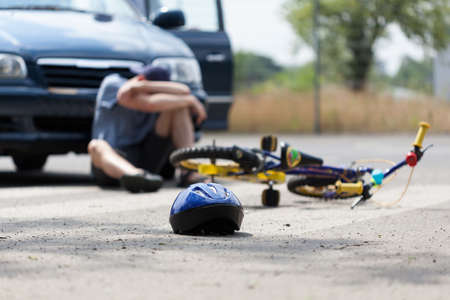 A boy suffering after a bike accident with a car photo
