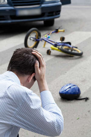A man worring about having hit a kid on a bike Stock Photo