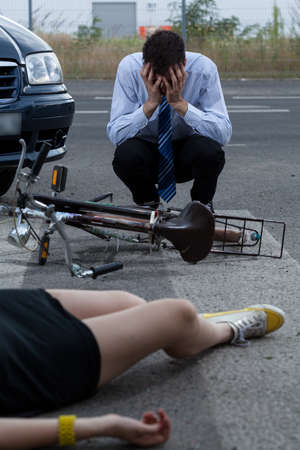 A man crying after hitting a woman on a bike