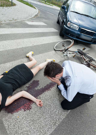 perpetrator: A dead woman lying on the road and a driver crying Stock Photo