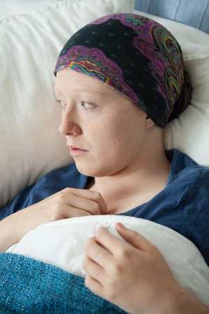 weakness: Young female patient with cancer in hospital bed Stock Photo