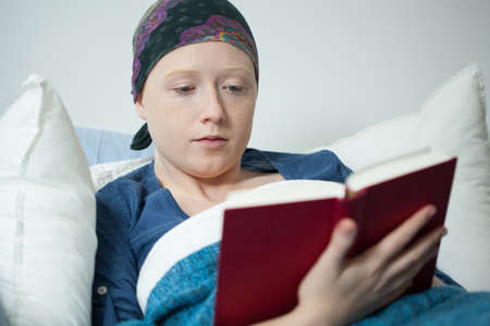 malignancy: Young cancer woman reading the book in hospital bed Stock Photo