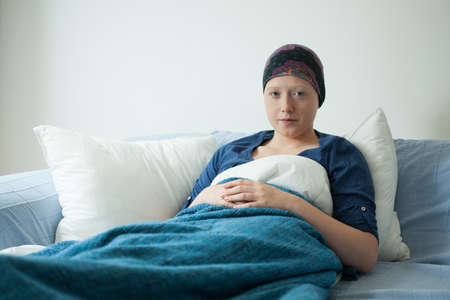bald girl: Pretty cancer girl lying in her bed in clinic Stock Photo