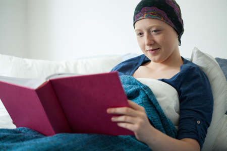 malignancy: Young sick woman with cancer browses her pink photo album Stock Photo