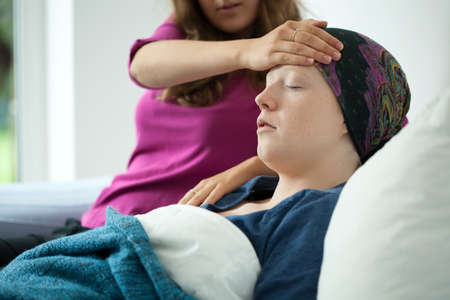 malignancy: Mom checking the temperature on her sick daughters forehead