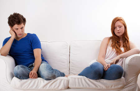 Young couple sitting on the sofa and being offended