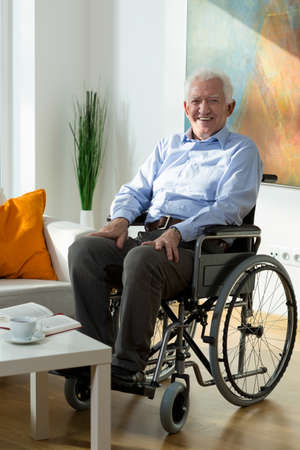 dignified: Elderly happy man sitting on wheelchair