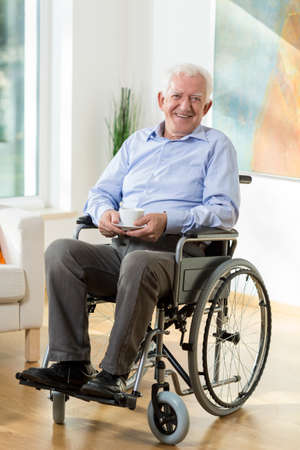 Older smiling man on wheelchair with cup of hot coffee Stockfoto