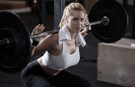Image of girl making squat with barbell Foto de archivo