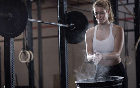 talcum: Horizontal view of girl preparing to weightlifting Stock Photo
