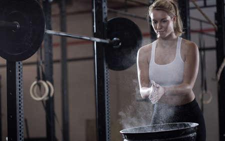 levantamiento de pesas: Vista horizontal de la chica que se prepara para el levantamiento de pesas