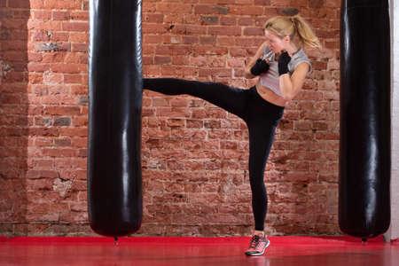 patada: encajar chica boxeo pateando saco de boxeo Foto de archivo