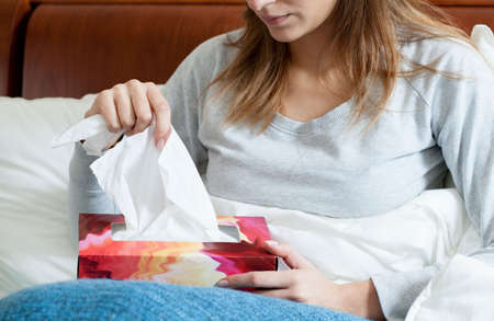 catarrh: Sick woman lying with box of tissues Stock Photo