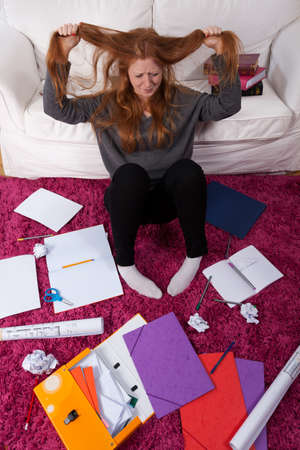 schoolwork: An unhappy girl made to study at home filled with schoolwork Stock Photo