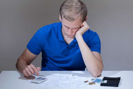 unpaid: Man with financial problems reading unpaid bills