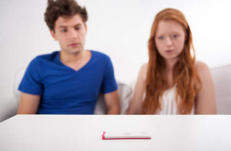 woman issues: Sad couple after doing of pregnancy test