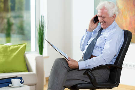 Elderly happy man in his office talking on the mobile phone