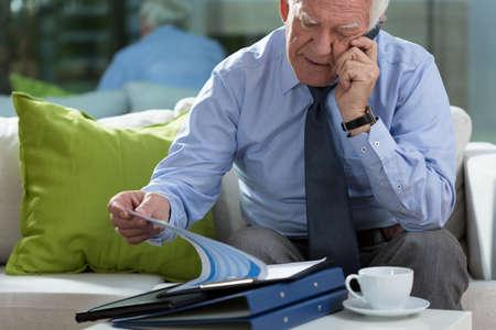 business case: Ouderen elegante man in zijn kantoor en zijn business case Stockfoto