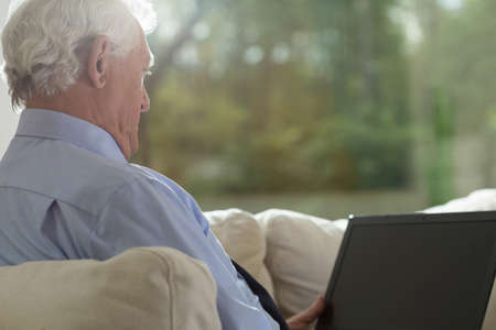 retirement homes: Aged man sitting on a couch and looking at the computer screen