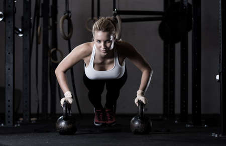 fitness: Fuertes chica haciendo flexiones jóvenes na kettlebells