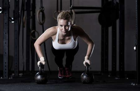 fitness: Junge starke Mädchen tun Push-ups na Kettlebells