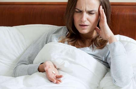 painkillers: Female having terrible headache taking painkillers