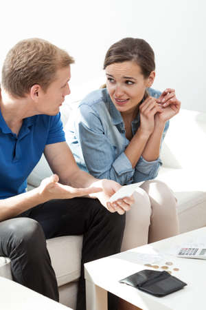 Vertical view of young couple arguing about money photo