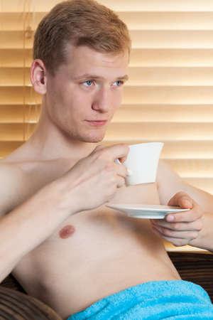 hombre tomando cafe: Hombre joven que bebe caf� en el spa, vertical