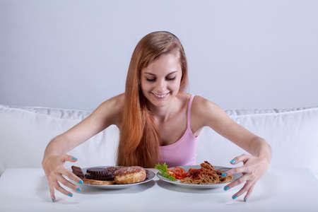 skinny girl: Young skinny girl binging on lots of food