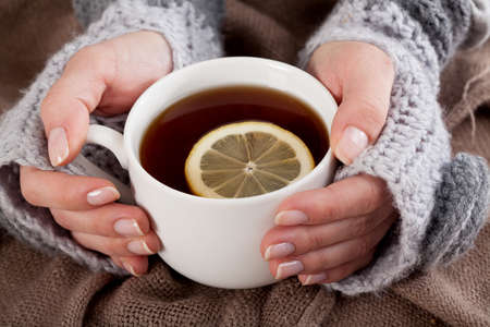 warm water: Womans hand holding cup of tea with lemon on a cold day Stock Photo