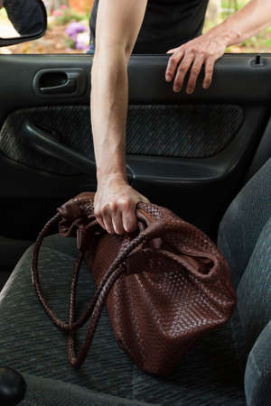 looting: Thief stealing womans bag from car, vertical