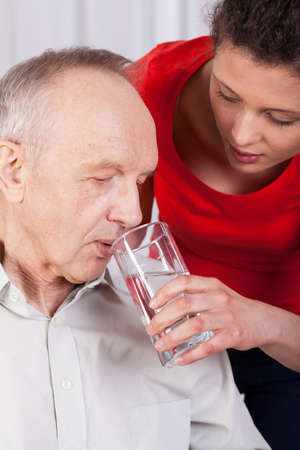 man drinking water: Nurse helping disabled man with drinking water Stock Photo