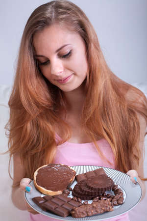 lifestyle disease: Portrait of girl holding a plate with chocolate snacks