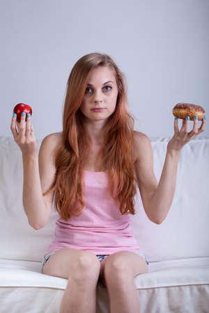 skinny girl: Skinny girl making choice between apple and doughnut Stock Photo