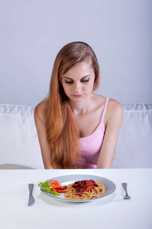 anorexia: Young girl sitting in front of dinner plate