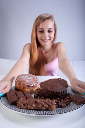 skinny girl: Young skinny girl holding a plate of sweets