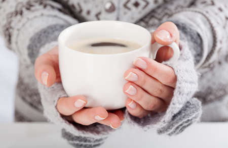 Close-up of a womans hand holding a cup of hot coffee Stock Photo
