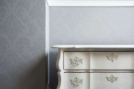 Close-up of retro style white sideboard in the corner Stock Photo
