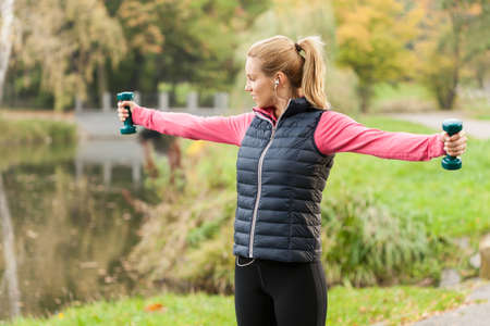 cold season: Young woman stretching with weights during morning jogging Stock Photo